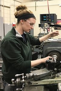 Bailey, a woman, working on a machine