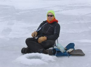 Brian Mason happily sits on his homemade ice fishing chair. He likes being closer to ice so he can be closer to the fish. Photo by Andy Kucera.