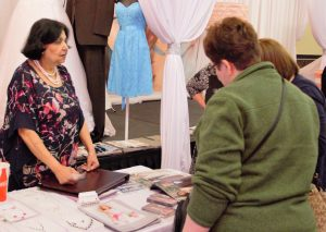 Two Hearts Owner Govinder Davgun chats with Jan Riopelle and Shawna Gjovik about her design and sewing business at the Bemidji Bridal Expo on Sunday. Davgun has been running her business for eighteen years and says she enjoys helping people to make their special day or a wonderful experience.